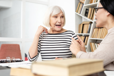 senior woman opening mouth to pronounce words with therapist