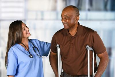 nurse guiding a senior man in crutches