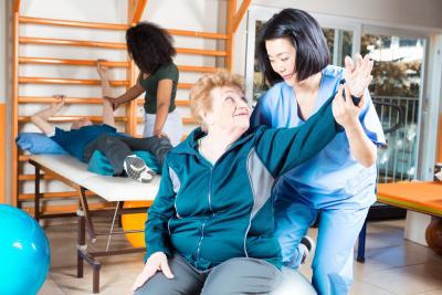 nurse guiding a senior during therapy