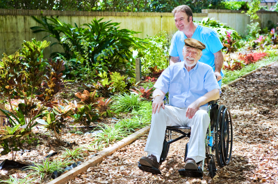 senior man and caregiver strolling at the garden